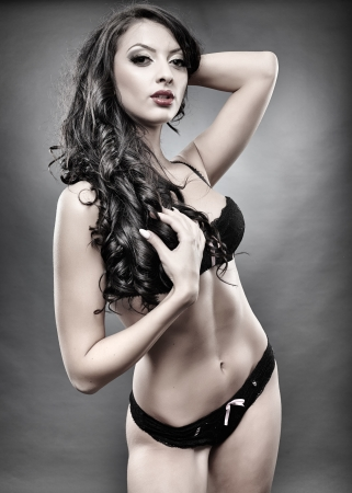 Studio shot of sexy brunette in black lingerie photo