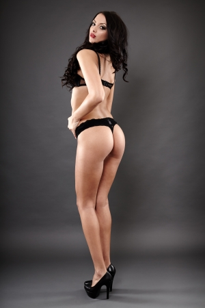 Full length studio portrait of alluring middle eastern wearing high heels and black lingerie with the back at the camera photo
