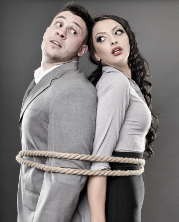 Studio shot of young couple back to back tied with a rope photo