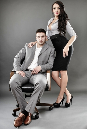 Studio shot of sexy secretary standing near the boss sitting on a chair photo