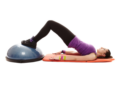 Studio shot of young athletic woman lying on the floor working out her legs and bottom on a bosu ball, isolated over white background photo