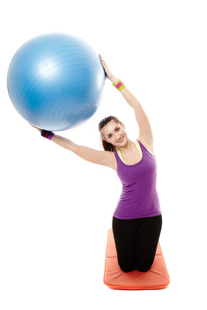 Studio shot of young athletic woman sitting on the floor and stretching with a ball, isolated over white background photo
