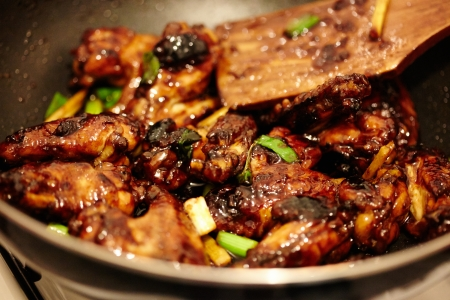 Closeup of asian caramel chicken wings in the pan on the stove, selective focus photo