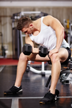 Shot of an athletic young man working his biceps with heavy dumbbells in the gym