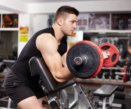 Young athletic man working his biceps at preacher curl bench at the gym photo