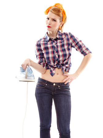 Sexy housewife holding a flat iron with hand on hip, isolated over white