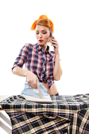 Sexy housewife talking to the phone while ironing, isolated over white photo