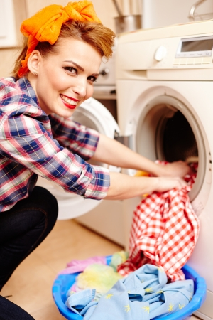 Closeup of cheerful housewife putting the laundry into the washing machine photo