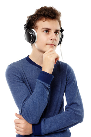 Studio shot of teenager with hand on chin listening to music at headphones, isolated over white background photo