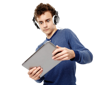 Studio shot of teenager listening to music at headphones and looking surprised at a tablet, isolated over white background photo