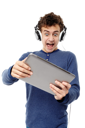 Studio shot of teenager listening to music at headphones and screaming while looking at a tablet, isolated over white background photo