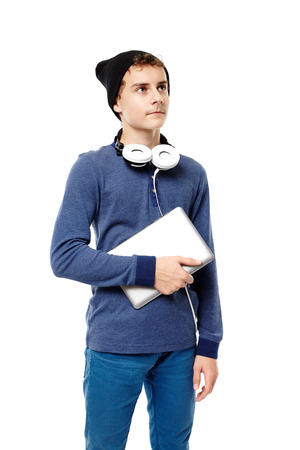 Studio shot of trendy teenager with cap and headphones over the neck holding a tablet, isolated over white background photo