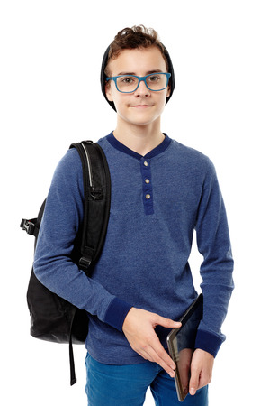 Studio shot of trendy teenager with backpack, wearing cap and glasses and holding a tablet, isolated over white background photo