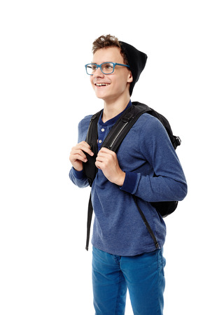 Studio shot of cheerful teenager with backpack wearing cap and glasses, isolated over white background photo
