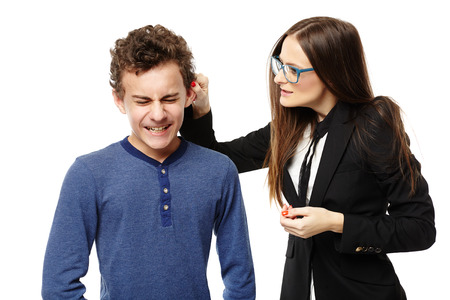 Studio shot of angry teacher grabbing students ear, isolated over white background photo