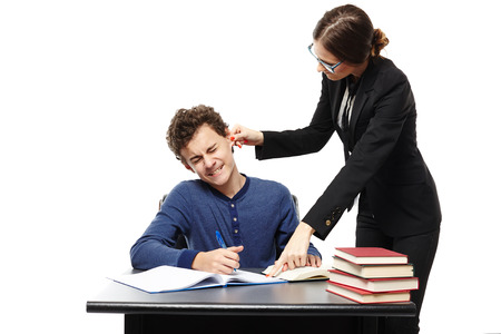 Studio shot of angry teacher twisting the student's ear and pointing him something in his notebook, isolated over white background