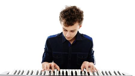 Studio photo d'une adolescente jouant un piano électronique, isolé sur fond blanc