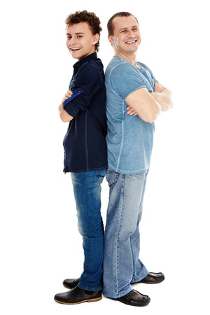 Father and son standing back to back isolated on white background, full length photo