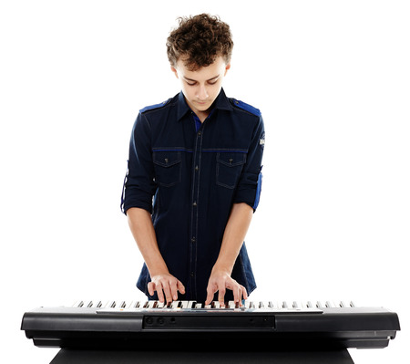 synthesizer: Studio shot of teenager playing an electronic piano, isolated over white background