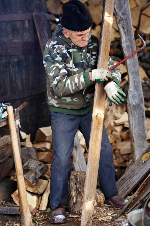 Senior man carpenter pulling nails out of a wood planck outdoor photo