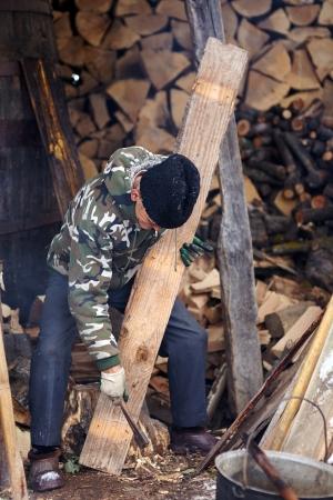 planck: Senior man carpenter pulling nails out of a wood planck outdoor