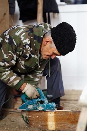 Senior man carpenter cutting the wood planck outdoor photo