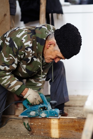 planck: Senior man carpenter cutting the wood planck outdoor