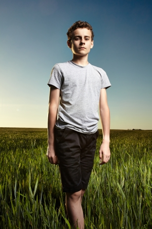 Portrait of a teenage boy in a green wheat field at sunset against clear blue sky photo