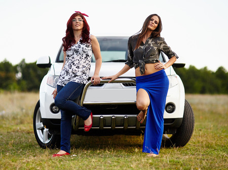Two beautiful young girls leaning against the bumper of an SUV car offroad photo