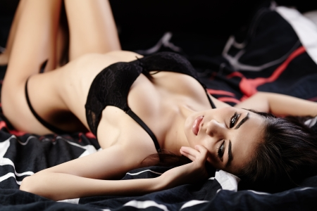 young girls breast: Studio shot of an attractive sexy brunette wearing black lingerie lying in bed