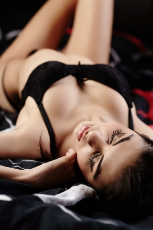 Studio shot of an attractive sexy brunette with eyes closed wearing black lingerie lying in bed photo