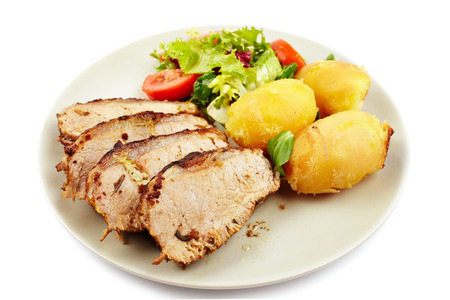 Closeup of a baked tenderloin  garnished with potatoes, lettuce and tomatoes on a plate