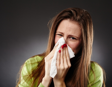 Young woman with bad cold blowing her nose in a white tissue