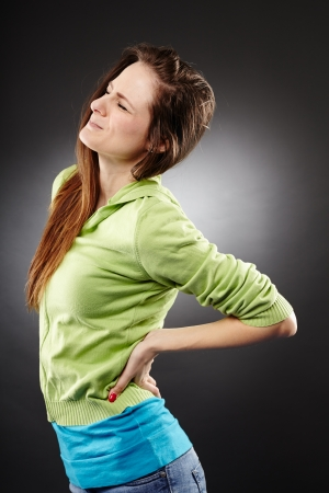 dorsalgia: Studio shot of a young woman having a severe lumbar pain over grey background