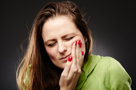Studio shot of a young woman having a severe tooth ache with hand on cheek over grey background