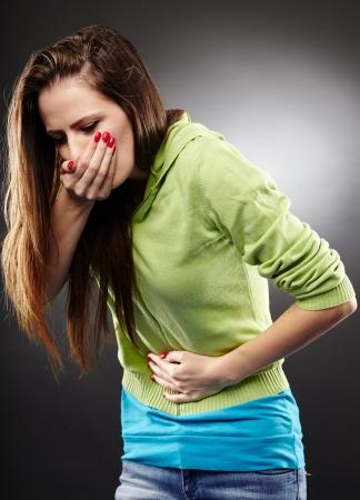 diarrea: Studio foto de una mujer enferma a punto de vomitar sosteniendo su estómago sobre fondo gris