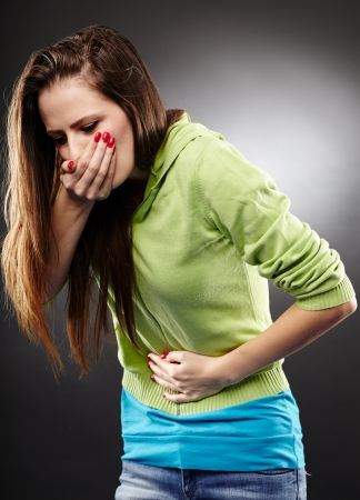 Studio photo d'une femme malade sur le point de vomir se tenant le ventre sur fond gris Banque d'images