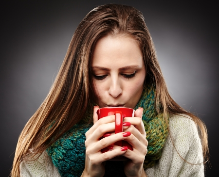 Closeup of  a woman with flu wrapped up in a scarf and drinking hot tea over gray background  photo