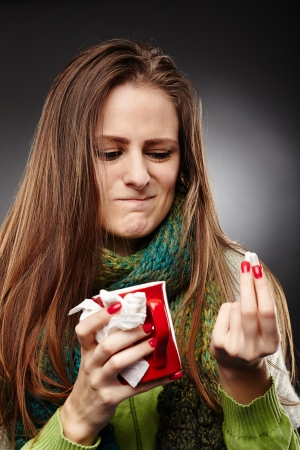 Closeup of a woman wrapped up in a scarf and holding a cup of hot tea expressing disgust to some drugs she is holding over gray background Stock Photo - 25084251
