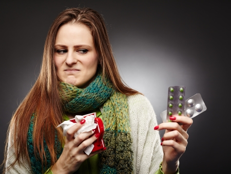 over packed: Studio shot of a woman holding a cup of hot tea and expressing disgust to some blister packed tablets she is holding over gray background