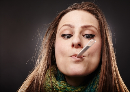 Closeup of a woman making a funny face while holding a thermometer in her mouth over gray background 写真素材