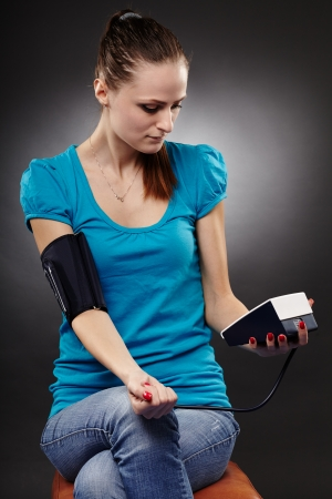 Studio shot of a woman measuring her blood pressure by herself over gray background photo