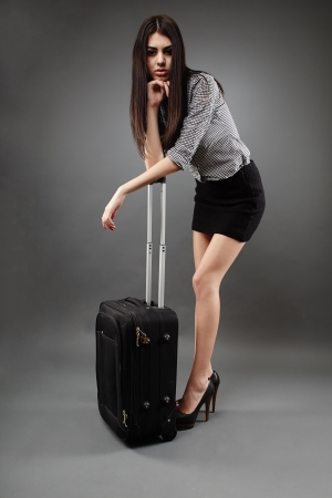 Beautiful young businesswoman with luggage over gray background, traveling concept photo