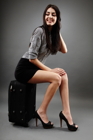 Studio shot of an attractive businesswoman sitting on her trolley and waiting photo