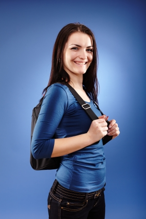 Portrait of a student girl with backpack on blue background  photo