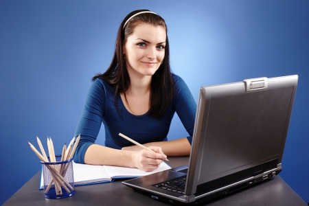 Portrait of a young woman working with laptop on blue background  photo