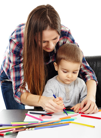 Young woman helping a cute toddler boy drawing with colorful pencils photo