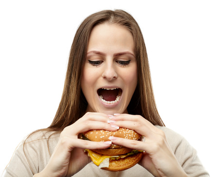 woman mouth open: Young caucasian woman preparing to bite a big burger, isolated on white background Stock Photo