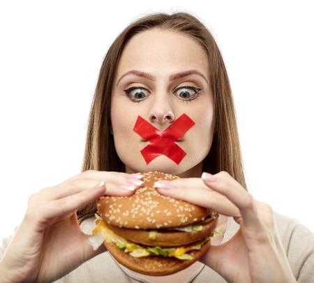 ni�a comiendo: Mujer joven con cinta adhesiva sobre su boca, impidi�ndole comer comida chatarra. Concepto de alimentaci�n saludable