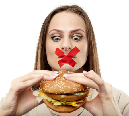 Young woman with duct tape over her mouth, preventing her to eat junk food. Healthy eating concept photo